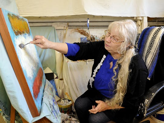 "Fleta Monaghan, painter, arts advocate and teacher, works in her studio at Riverview Station in this 2013 photo. She is a co-curator of the exhibit ""An Artful Life."""