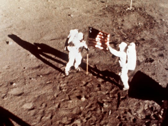 """Apollo 11 astronauts Neil Armstrong and Edwin E. """"Buzz"""" Aldrin, the first men to land on the moon, plant the U.S. flag on the lunar surface, July 20, 1969."""