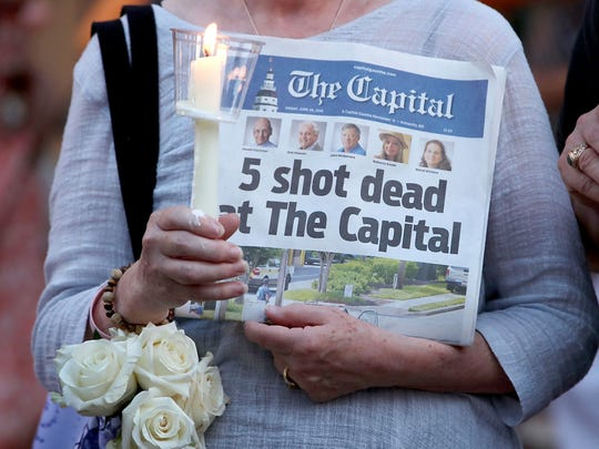 A women holds today's edition of the Capital Gazette