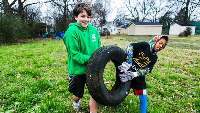 """Ben Turner (left), 12, and Antrayvon Jones, 11, carry a used tire to the curb on Ash St. during a Memphis Kings and Clean Memphis cleanup in the Douglass neighborhood on Saturday morning, Feb. 18. 2017. The organizations teamed up to shine a positive light on young African-American teens in Memphis. """"Everyday we get new opportunities to teach kids what community is about,"""" said Sam Davis, CEO and founder of Memphis Kings Youth Organization. """"I tell everybody I meet, you know, in order to change the world the only thing you got to do is change your world. Change the world you live in and you will be changing the world."""""""