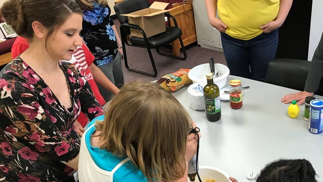 Theresa Hanntz, Somerset County 4-H Healthy Living Program coordinator, helps children enrolled in the Catholic Charities TAP program prepare a healthy snack.