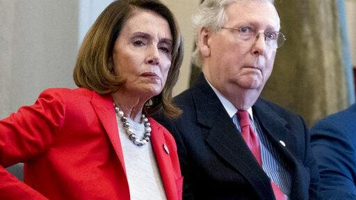 In this March 21, 2018, file photo Nancy Pelosi of Calif.,  and Senate Majority Leader Mitch McConnell of Ky., attend a Congressional Gold Medal Ceremony honoring the Office of Strategic Services in Emancipation Hall on Capitol Hill in Washington. Pelosi and McConnell are coming together to see if a deal can be made to stop billions of dollars in government spending cuts. Failure to reach an agreement would usher in cuts to the Pentagon and domestic programs of $125 billion next year _ a 10 percent drop from current levels.
