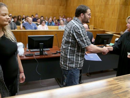 Nathan Hempel, center, gets a handshake from Kitsap