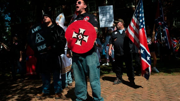 A member of the Ku Klux Klan shouts at counter protesters