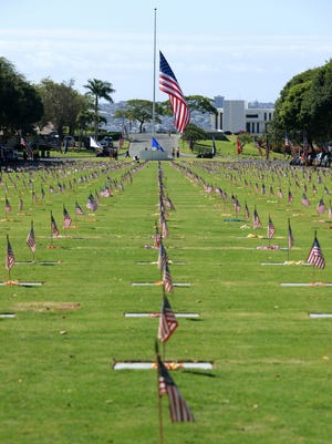 Gravestones at the National Memorial Cemetery of the Pacific at Punchbowl are decorated with American flags and Hawaiian leis during Memorial Day.