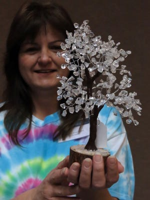 At the Elements of Divine Wisdom booth Lori McDaniel displays a chakra gem stone tree during the Life Spirit and Health Metaphysical Expo being held through Sunday at the Crowne Plaza Pensacola Grand Hotel.