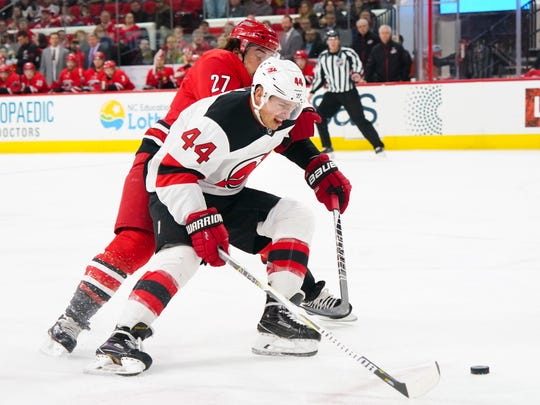 Mar 2, 2018; Raleigh, NC, USA;  New Jersey Devils forward Miles Wood (44) skates with the puck past Carolina Hurricanes defensemen Justin Faulk (27) during the first period at PNC Arena.