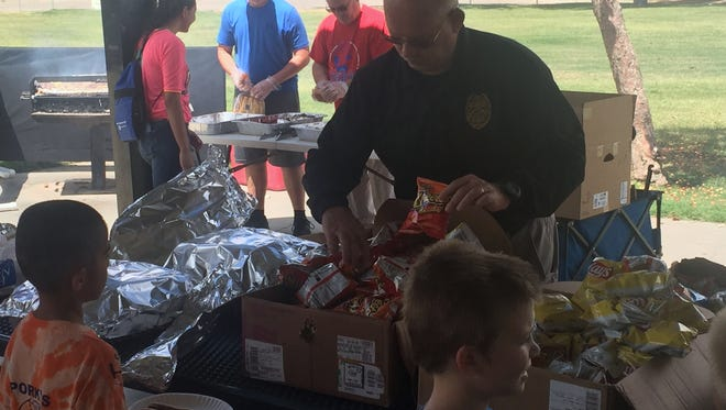Deputy Police Chief Roger Schoolcraft helps serve food to the Boys and Girls Club of Otero County children.
