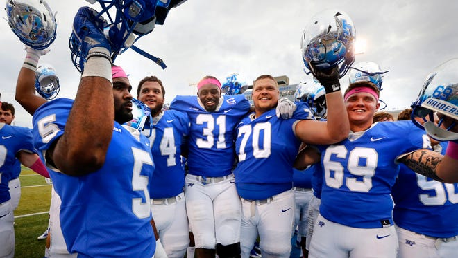 MTSU football players Jocquez Bruce (5), Robert Behanan (74), DJ Sanders (31), Conner Trent (70) and Daniel Sargent (69) celebrate their 37-17 win over FIU with the team after the game, on Saturday, Oct. 7, 2017, at MTSU.