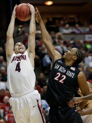 Arizona guard T.J. McConnell (4) rebounds next to San Diego State forward Josh Davis (22) during the first half of an NCAA men's college basketball tournament regional semifinal.