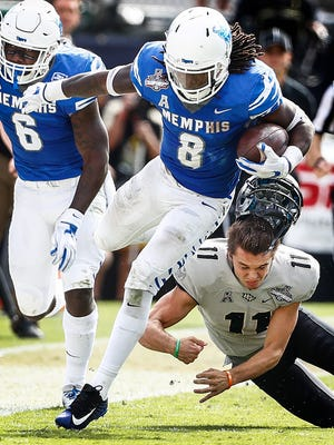 Memphis kick returner Darrell Henderson (left) runs by UCF kicker Matthew Wright (right) during second quarter action of the the AAC Championship football game in Orlando, Fl., Saturday, December 2, 2017.