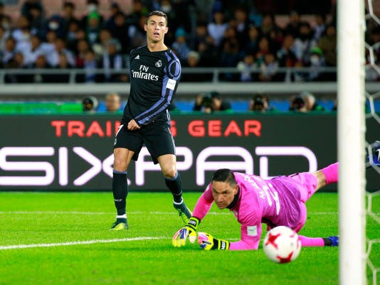 Real Madrid's Cristiano Ronaldo makes a shoot attempt as Club America's goalkeeper Moises Munoz looks at the ball during their semifinal match at the FIFA Club World Cup soccer tournament in Yokohama, near Tokyo, Thursday, Dec. 15, 2016. (AP Photo/Shizuo Kambayashi)