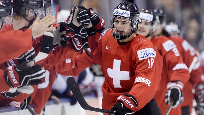 Switzerland forward Nico Hischier (18) celebrates with teammates at the bench after scoring against the United States during the third period of a quarterfinal game at the world juniors.