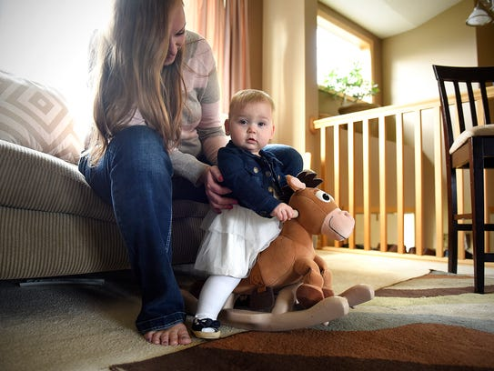 Shannon Feuling holds her daughter Claire on a rocking