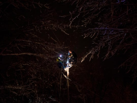 A Local 104 crew with Grattan Line from Mass. works to restore power to a section of Raceway Road in Jericho late Friday night.