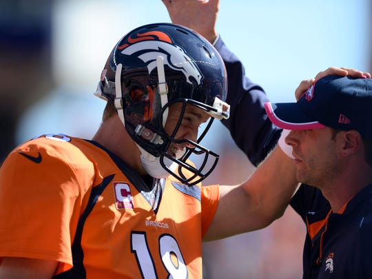 Oct 5, 2014; Denver, CO, USA; Denver Broncos quarterback Peyton Manning (18) reacts to his 500th touchdown pass with quarterback coach Adam Gase in the first quarter against the Arizona Cardinals at Sports Authority Field at Mile High. Mandatory Credit: Ron Chenoy-USA TODAY Sports