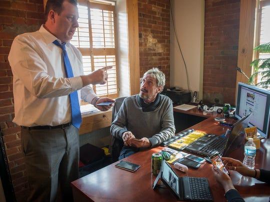 John McAfee, center, speaks with business partner Tom