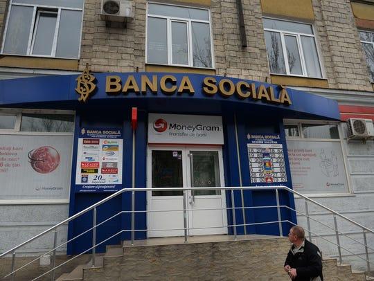 A man looks at a Banca Sociala branch in Chisinau,
