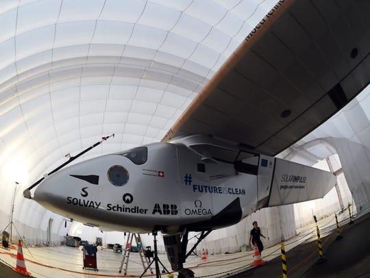 A ground crew member walks near the solar-powered airplane