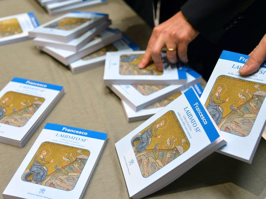 People hold copies of Pope Francis' encyclical on climate