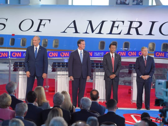 Republican presidential candidates, former New York Gov. George Pataki, left, former Pennsylvania Sen. Rick Santorum, second from left, Louisiana Gov. Bobby Jindal, second from right, and Sen. Lindsey Graham, R-S.C., take the stage in the early CNN Republican presidential debate at the Ronald Reagan Presidential Library and Museum on Wednesday, Sept. 16, 2015, in Simi Valley, Calif. (AP Photo/Mark J. Terrill)