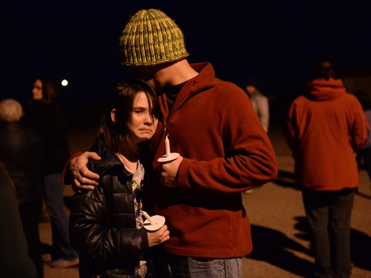 Andrew Laviolette hugs his daughter Zoee Laviolette at a vigil to support the families of two 11-year-olds who died by suicide on Tuesday, November 24, 2015.