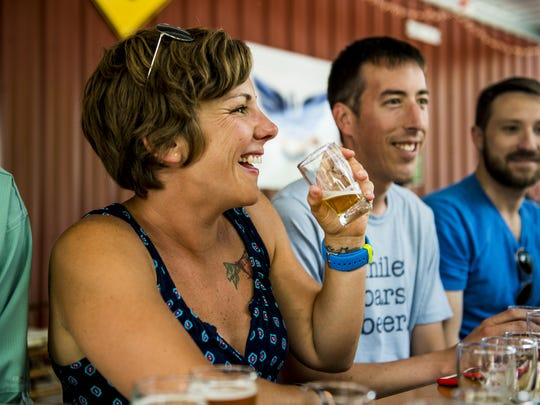 Megan Brummer sips a beer while conversing with friends