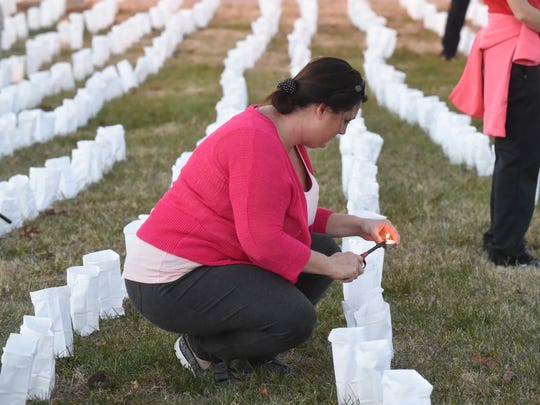 A woman helps light candles at the Hospice House. The 3,000 luminaries flickering outside Thursday, Dec. 10, 2015 represented the first 3,000 patients the Hospice House has served since opening in 2005. Hospice of the Ozarks commemorated the facility's 10th anniversary with an event in Mountain Home.