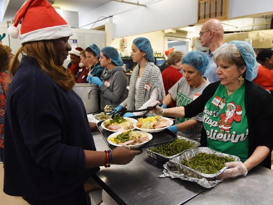 Volunteers Ralphelene Rojas, left, and Marlene Ulman, right, prepare plates of food for patrons of the annual Eileen Hickey Holiday Dinner in 2015.