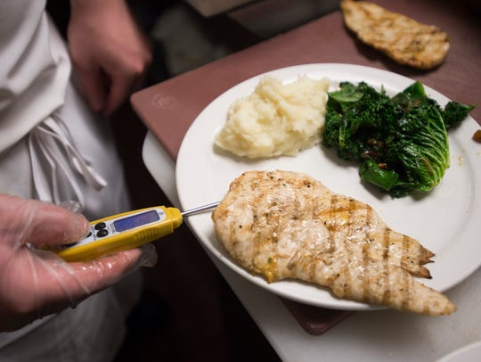 The internal temperature of a cut of chicken is taken by a Larimer County health inspector.
