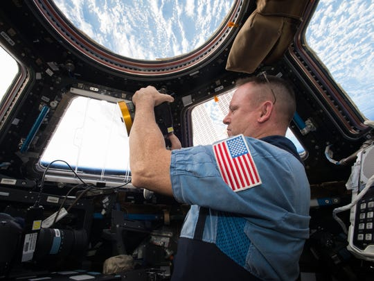 NASA Commander Butch Wilmore shoots a scene with the IMAX camera through the Cupola Observation Module of the International Space Station.