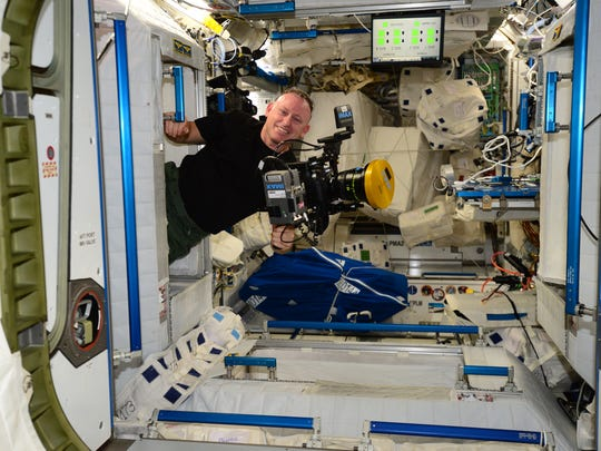 "On board the International Space Station, NASA Commander Barry ""Butch' Wilmore poses with the IMAX camera."