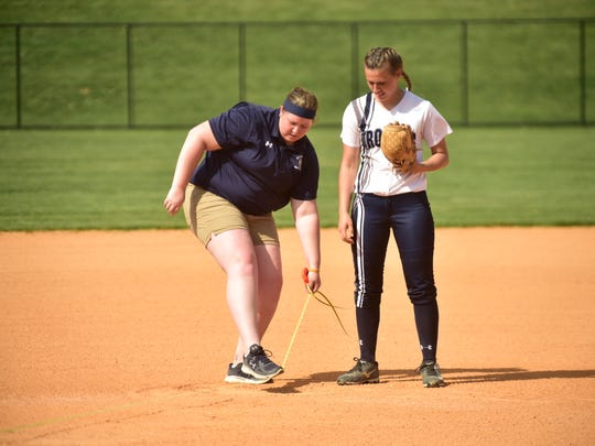 Chambersburg pitching coach Emily Estep, left, helps pitching ace Laken Myers warm up for the Mifflin County game, Tuesday, April 26, 2016. Estep is a former Trojan player.