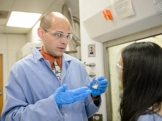 Clemson researcher Andrew Tennyson discusses the new compound with student Qingzhao An