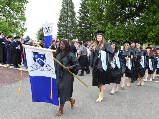 Graduates of Mount Saint Mary College in Newburgh walk to commencement on campus.