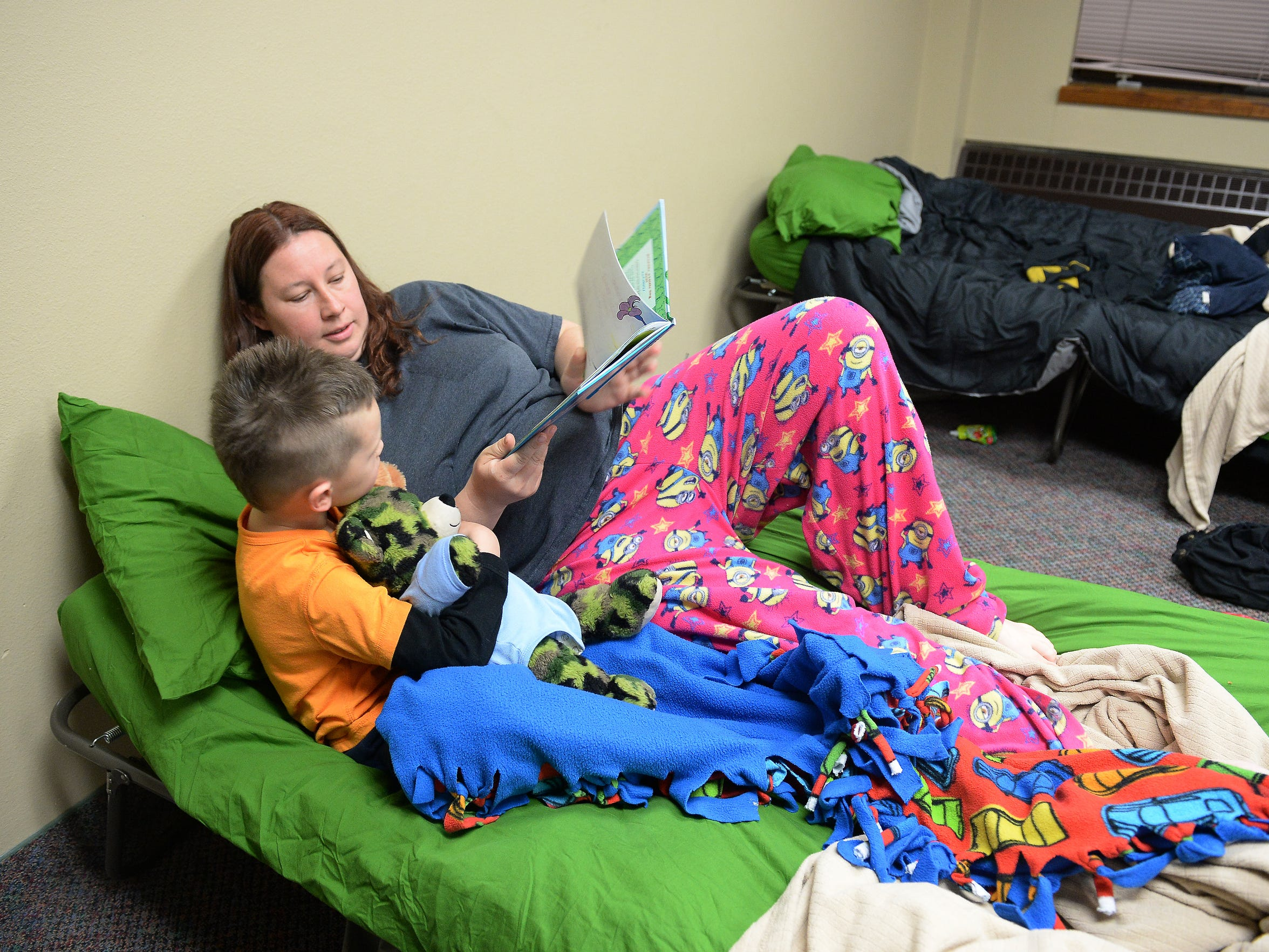 Fawn Martin reads a bedtime story to her son, Zayden, in the Sunday school classroom that serves as their bedroom for the week at Summitview Church on March 15, 2016.