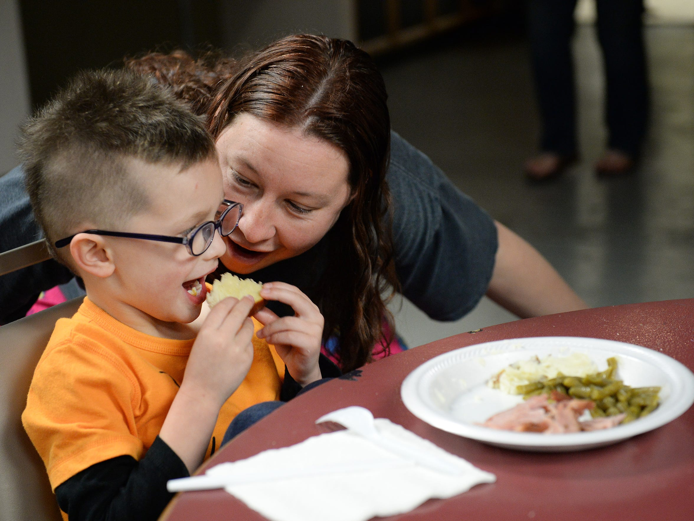 Fawn Martin pretends to eat her son, Zayden's, dinner at Summitview Church on March 15, 2016. Dinner is prepared by volunteers each night for families in the Faith Family Hospitality program.