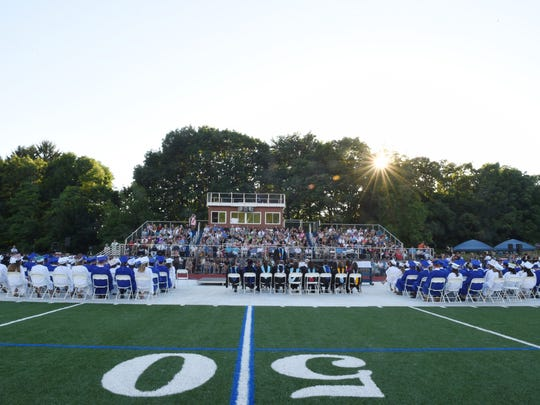 Millbrook High School seniors, faculty and staff sit before a crowd at Millbrook High Sschool for commencement on Friday.
