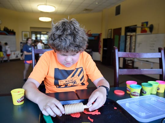 A camper manipulates Play-Doh at the Summer Treatment