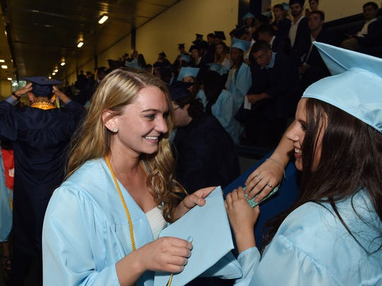 John Jay High School seniors, from left, Bridget Diedrich and Meghan Murray chat before lining up for commencement at the Mid-Hudson Civic Center on Friday.