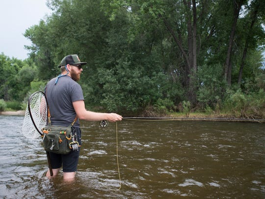 Todd Dewitt wades into the Cache la Poudre River while fly fishing Wednesday near the Shields Street bridge in Fort Collins