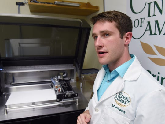 Liam MacLeod, the Culinary Institute of America's additive manufacturing specialist, describes the process of how he uses the printer in the background to create edible 3D printed items inside the CIA's 3D Printing Lab on Thursday.