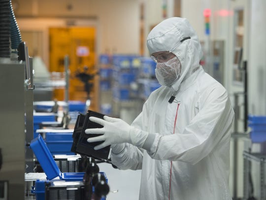 A man works in one of the manufacturing labs at Avago