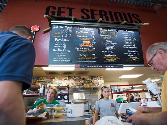 Customers make their selections of brisket, sausage