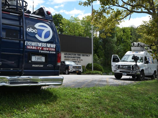 News vans stand parked outside of the Arlington Fire District Headquarters off Route 44.