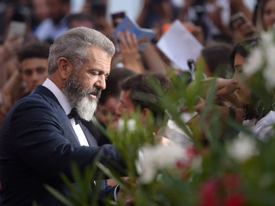 Director Mel Gibson signs autographs as he arrives
