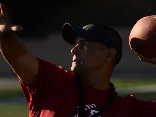 Santa Paula head coach Mike Montoya throws the ball during a Cardinals' practice. Santa Paula plays at rival Fillmore on Saturday night.