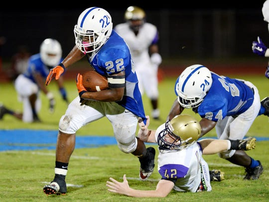 Sebastian River High School's Anthony Parks (22) shakes a tackle from Okeechobee High School's Bracen Harvey, Friday, Sept. 16, 2016 during a District 14-6A game in Sebastian. The Sharks won 35-0 to remain undefeated on the season.