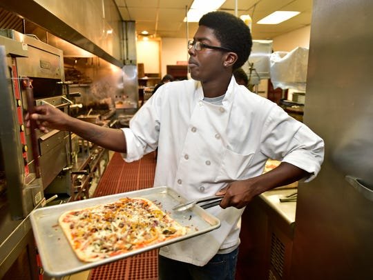 Jordan Thompson takes a pizza from the oven on Tuesday,