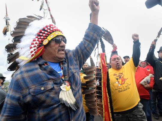 JR American Horse, left, raises his fist with others while leading a march to the Dakota Access Pipeline site in North Dakota on Friday, Sept. 9. Several hundred protesters marched from a protest camp to the pipeline site, where some archaeological artifacts have been discovered.